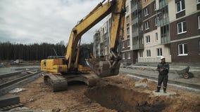 Sabbia di scavatura dell'escavatore giallo lento in fossa al cantiere stock footage