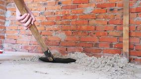 Sabbia di scavatura della vanga davanti al muro di mattoni Sabbia professionale di vangate degli artigiani con la pala Concetto d stock footage