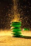 Sabbia dorata che cade sull'equilibratura delle pietre verdi immagine stock