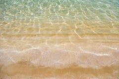 Sabbia dorata ed acqua trasparente, struttura Immagini Stock