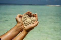 Sabbia a forma di del cuore in mani della donna Fotografie Stock Libere da Diritti