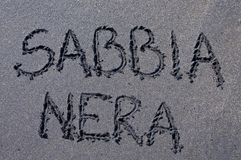 Sabbia Nera black sand inscription drawn on black sand. Italian text `Sabbia Nera` black sand inscription drawn on a black sand beach near Canggu, Bali royalty free stock images