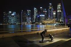 Sabbie della baia del porticciolo, Singapore La scultura di due bambini con i grattacieli nei precedenti Immagine Stock