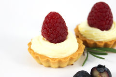 Saber with custard and raspberries. Saber with custard under fresh raspberries Royalty Free Stock Photo