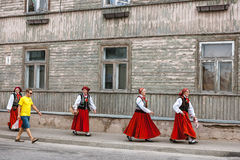 SABILE, LATVIA - JULY 28 2012: Four women in traditional latvian folk costumes walk down the street of Sabile and looks at the yo Stock Photography