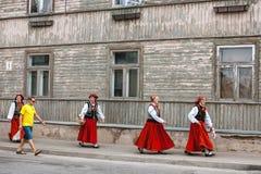 SABILE, LETLAND - JULI 28 2012: Vier vrouwen in traditionele Letse volkskostuums lopen onderaan de straat van Sabile en bekijkt y Stock Fotografie