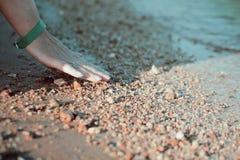 Sable émouvant de plage de la main de la femme Photo stock