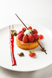 Sable breton or Breton shortbread with vanilla cream and raspberry coulis on white dish.  royalty free stock photography