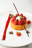 Sable breton or Breton shortbread with vanilla cream and raspberry coulis on white dish.  royalty free stock image