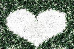 Sable de cadre d'herbe verte dans la forme de coeur Image stock