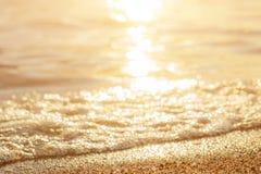 Sable de mer humide sur la plage contre le beau coucher du soleil d'or de fond photos libres de droits