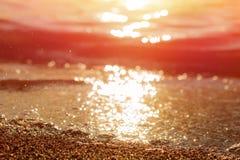 Sable de mer humide sur la plage contre le beau coucher du soleil d'or de fond image libre de droits