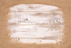 Sable de plage sur le fond en bois Photographie stock libre de droits