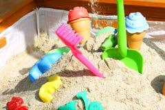 Sable en baisse dans le bac à sable Divers jouets dans différentes couleurs C image stock