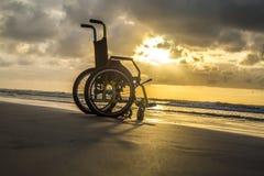 Sable enfantin d'horizon de fauteuil roulant de coucher du soleil photo libre de droits