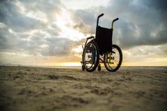 Sable enfantin d'horizon de fauteuil roulant de coucher du soleil photos libres de droits