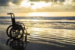 Sable enfantin d'horizon de fauteuil roulant de coucher du soleil image stock