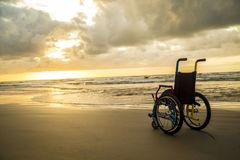 Sable enfantin d'horizon de fauteuil roulant de coucher du soleil photographie stock