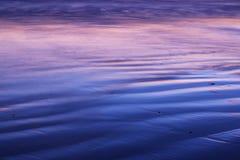 Sable et vagues au coucher du soleil Photo stock