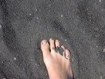 sable noir de pied de plage Image libre de droits