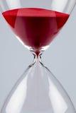 Sable rouge dans un sablier, vertical Images stock