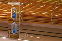Sablier en verre avec le sable bleu à l'intérieur à la nuance des abat-jour en bois Photos stock