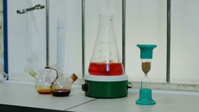 Sablier et flacon avec le liquide dans le laboratoire médical