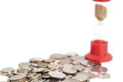 Sablier sur des pièces de monnaie Photographie stock libre de droits