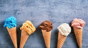 Sabores sortidos do gelado nos cones em uma bandeira fotos de stock