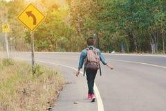 Sac à dos asiatique heureux de garçon à l'arrière-plan de route et de forêt Photo stock