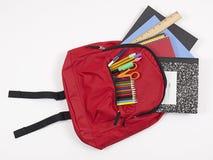 Sac à dos avec des approvisionnements d'école se renversant à l'extérieur image stock