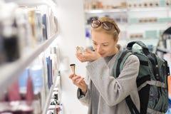 Sac à dos de port de voyage de jeune voyageur féminin blond choisissant le parfum dans le magasin hors taxe d'aéroport photo stock