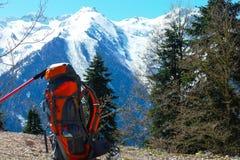 Sac à dos et poteau de trekking sur un fond des montagnes se reposant sur une falaise de montagne Photographie stock libre de droits