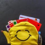 Sac à dos jaune d'école avec des accessoires sur le fond noir images stock