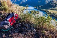 Sac à dos rouge de touristes se trouvant à l'herbe au bord de la côte de rivière Image libre de droits