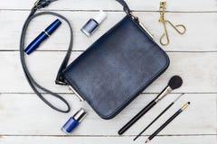Sac à main bleu-foncé et maquillage bleu Configuration plate Images libres de droits
