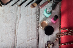Sac à main femelle avec des cosmétiques et mobile sur le bois blanc Images stock