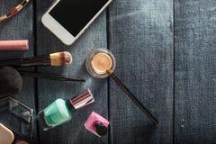 Sac à main femelle avec des cosmétiques et mobile sur le fond de jeans Images stock