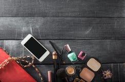 Sac à main femelle avec des cosmétiques et mobile sur le fond de jeans Image stock