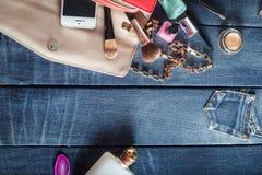 Sac à main femelle avec des cosmétiques et mobile sur le fond de jeans Image libre de droits