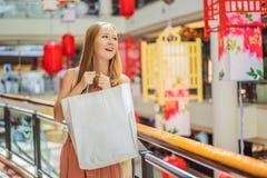 Sac à provisions de prise de femme dans la perspective des lanternes rouges chinoises pendant la nouvelle année chinoise Grande v photos stock