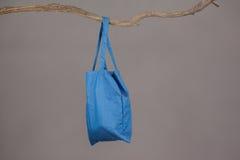 Sac bleu accrochant sur une branche d'arbre Image stock