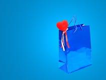 Sac bleu de cadeau de jour de valentines et coeur rouge sur le backg bleu Photos stock