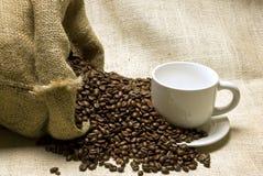 Sac complètement des haricots avec la tasse et la soucoupe de café Image stock