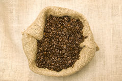 Sac complètement des haricots avec la tasse et la soucoupe de café Photos stock