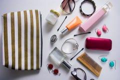 Sac cosmétique rayé avec de divers produits cosmétiques sur un fond blanc image libre de droits