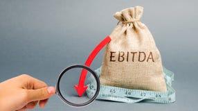 Sac d'argent avec le mot Ebitda et en bas de flèche Revenus avant int?r?t, imp?ts, d?pr?ciation et amortissement Probl?mes avec images stock
