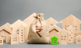 Sac d'argent avec une roupie de roupie indienne de signe et des maisons en bois Le concept du marché de l'immobilier Évaluation e images libres de droits