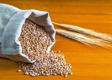 Sac de blé et des oreilles sur un fond en bois Photos libres de droits