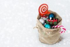Sac de cadeau du ` s de Santa complètement des jouets et des cadeaux sur la neige Copiez l'espace Images stock